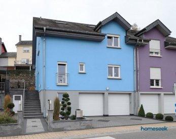 (renseignements et visites : +352 661 409 627 ) PROCHE LAROCHETTE (5km) : ERMSDORFF Homeseek Limpertsberg vous présente en exclusivité cette maison récente entièrement équipée et aux finitions soignées.  Construite sur un terrain de 3 ares, elle développe une surface utile de +/- 350 m² dont +/- 252 m² habitables. Située au calme cette maison en excellent état offre un vaste salon séjour (38 m²) et une cuisine équipée ouvrant sur la terrasse et le jardin,  5 chambres dont une suite parentale et un bureau. Sous-sol complet avec 2 garages (4 places). Aucun travaux à prévoir.  Possibilité d'y aménager un espace pour votre activité professionnelle    Description détaillée :  Au rez de chaussée : un hall d'entrée, un salon séjour ouvrant sur la terrasse et le jardin, une cuisine équipée KICHECHEF avec accès terrasse, une chambre (13 m² avec possibilité d'ouverture pour 'agrandir le séjour), un bureau, un wc. (possibilité d'ouvrir la cuisine sur le séjour) Au 1er étage : un hall, une suite parentale (24m²) disposant d'une salle de bains privative, 2 chambres (20 m²), une salle de bains meublée (baignoire, douche, wc, urinoir, double vasque). Au 2ème étage : un hall, 1 chambre, une pièce de rangement transformable en salle d'eau. (possibilité de créer un studio, conduite en attente pour la création d'une cuisine) Au sous-sol : 2 garages avec portes motorisées (jusqu'à 4 véhicules), 2 caves, une chaufferie, wc. A l'extérieur : terrasse, jardin paysagé avec abri, local de rangement, 2 emplacements de stationnement.  Prestations : Cuisine équipée Kichechef, volets motorisés, salles de bains meublées, escaliers en granit, isolation par l'extérieur, espaces de rangement aménagés.  Ref agence :4921731