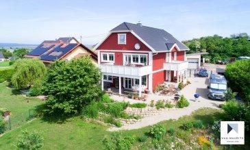 Situation  Bilzingen est une charmante petite communauté d'origine à l'histoire agricole, à environ 30kilomètres au sud-ouest de Trêves. Ce bijou entre campagne et montagne de l'Argovie n'est qu'à six kilomètres de la frontière avec le Luxembourg. Idéalement vous vivrez dans un environnement idyllique et reposant, à quelques minutes en voiture de zones d'activité, commerces et points de service urbains.  Description  À Bilzingen, maison unique de style scandinave, architecture suédoise (Sjödalshus) en bois massif, construite en 2016. Une maison familiale originale et chaleureuse de 340m², avec 5chambres et un beau jardin de 1400m² sans aucune mitoyenneté, en plein cœur du paysage naturel. Avec garage double, parking 4voitures, terrasse, 2balcons, cheminée, coin barbecue et deux saunas. Cette maison lumineuse et confortable est entièrement équipée avec 15pièces spacieuses, dont de nombreuses comportent des espaces semi-ouverts.  Les chambres avec dressings et 2 salles de bain sont sur deux étages, ce qui laisse la possibilité aux familles d'avoir des pièces de vie plus tranquilles pour les enfants ou adolescents, ou pour les invités.  Les points forts   Pour les amoureux du style scandinave Depuis quelques années, les maisons de style nordique, en bois massif, remportent un grand succès. Leur architecture est à la fois respectueuse de l'environnement, contemporaine, extrêmement sobre et élégante, et offre un habitat sain et écologique.   Le look de cette maison est celui d'une habitation harmonieuse, parfaitement intégrée dans un cadre naturel et un paysage apaisant.  Construction écologique à économie d'énergie (système géothermique et citerne d'eau de pluie, ossature extérieure bois, poêle à bois, triple vitrage…). Certifiée «Passeport énergétiqueA+».  Un commission d'acheteur d'un montant de 3.51% sur le prix d'achat TTC est  percue et due de la signature du contrat par un notaire.   Haus für zwei Generationen, gebaut 2016 von dem schwedischen Hersteller Sjödalshu