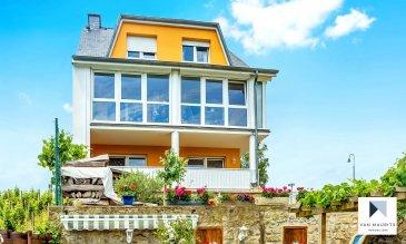 Située dans le village de Grevenmacher, près du stade avec vue imprenable sur la Moselle, cette maison datant de 1995 a connu plusieurs phases de rénovation, la plus importante ayant eu lieu en 2017.   Elle se compose comme suit :  Le rez-de-chaussée s'ouvre sur un hall ± 10 m² desservant un séjour ± 26 m², une cuisine équipée ± 13 m², un wc séparé ± 2 m². La cuisine et le séjour donnent accès à une véranda isolée ± 18 m² profitant d'une vue sur la Moselle et ses alentours.  Un garage pour deux voitures ± 29 m² complète ce niveau.  Le 1er étage se compose d'un palier ± 10 m² desservant trois chambres de ± 16, 17 et 22 m², une salle de bain ± 13 m² et une salle de douche ± 6 m².  Les combles isolés et aménagés comprennent deux chambres de ± 25 et 16 m² ainsi qu'une salle de douche ± 5 m².  Le 1er sous-sol comprend un appartement indépendant avec accès privatif composé d'un hall d'entrée ± 7 m², d'un studio ± 26 m², d'une cuisine équipée ± 9 m² et d'une salle de douche ± 4 m².  Ce niveau dispose également de plusieurs caves, d'une buanderie et d'un débarras, le tout sur une suface de ± 28 m². Une terrasse extérieure ± 16 m² complète ce niveau.  Le 2ème sous-sol (rez-de-jardin), se compose d'une cave ± 16 m² et de la chaufferie ± 25 m² (chaudière Buderus neuve (2017) et deux citernes à mazout de 2000 litres chacune).  Généralités : - Maison en bon état ; - Joli jardin soigné avec vue dégagée sur la Moselle ; - Deux emplacements de parking à coté de la maison ; - Proche de toutes commodités (gare, commerces, écoles, autoroute, ...).