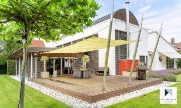 C'est en 1995 que cette belle maison d'architecte a été construite sur un terrain de 32ares et 70 centiares dans un quartier résidentiel et verdoyant de Moutfort.  Bâtie dans un esprit écologique avant-gardiste avec des matériaux de qualité, ses 360m² habitables sur un total de ± 415 m² présentent de nombreux attraits qui devraient faire le bonheur d'une famille.  Elle se compose comme suit: Au rez-de-chaussée:  Une entrée de ± 10m² avec vestiaire et toilette d'invités, un hall ±5m² conduit vers un sauna et douche ± 11m², une chambre ±12m², une buanderie ±6m², une salle de bains ±10m², un bureau/bibliothèque ±12m², une cuisine équipée et aménagée ±32m² ouverte sur un spacieux séjour ± 92m².  Très lumineux, ce dernier est composé d'un salon (10m de haut) et sa cheminée, d'une salle à manger, d'une véranda avec grandes baies vitrées et puits de lumière, l'ensemble donnant sur le jardin et la terrasse d'environ 125m². Le garage ±35m² peut abriter 2 voitures. Une salle de fitness avec équipements et insonorisée a été installée en mezzanine.  Au 1er étage: Une salle de douches ±6m² avec douche à l'italienne, double vasques, wc et bidet, une chambre avec mezzanine ± 17m² séparée par un couloir ±6m² de la suite parentale ± 21m² avec dressing ±15m² et salle de bains ±10m² et d'une chambre de ± 29m².  Le parc, aménagé, est agrémenté d'une grande pelouse, de sculptures, d'un terrain de pétanque et divers arbres dont des arbres fruitiers (quetsches, mirabelles, pommes). L'arrosage se fait via l'eau du puits ou par pompage dans l'étang. Autorisations disponibles pour des extensions pour piscine et clubhouse.  Détails supplémentaires:  - Possibilité achat 7 ares supplémentaires, terrain non constructible:   450.000€ - Isolation: Blocs KBL - Système d'alarme: Teleguide Intelligent Security (Rolling Code); - 3 abris de jardin: atelier électricité, abri pour le tracteur, stockage du bois; - Chaudière gaz de ville; - Sauna et solarium de marque Klafs;