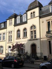 Située sur le prestigieux boulevard de la Pétrusse à Luxembourg-ville, cette magnifique maison de charme datant de 1910, soigneusement préservée dans ses décors d'origine lors des restaurations, présente une surface habitable de ± 252 m² pour une surface totale utile de plus de 300 m², plus terrasse et balcon.  La propriété se compose comme suit:  Au rez-de-chaussée, le hall d'entrée conservé dans son état d'origine, cartactérisé par des faïences aux murs, carreaux décorés d'époque au sol, cage d'escaliers en bois sculpté et plafond avec moulures authentiques, dessert un spacieux salon-salle à manger en enfilade avec parquet d'époque donnant sur un balcon/terrasse avec vue surprenante sur la vallée de la Pétrusse. La cuisine équipée, adjacente au salon, dispose d'un passe-plat vers la salle à manger. Ce niveau profite d'une belle hauteur sous plafond de 3,40 m.  Le 1er étage est introduit par un palier avec vitraux décorés d'origine desservant deux grandes chambres avec moulures authentiques au plafond, un dressing et une salle de bain avec baignoire, douche, lavabo, bidet et wc. Un petit balcon accessible via la plus grande chambre complète l'étage. Parquet d'origine à tout l'étage. Très belle hauteur sous plafond d'environ 3,30 m.  Le 2ème étage s'ouvre sur un palier desservant trois chambres et une salle de bain avec poutres apparentes.  La maison dispose, au dernier étage, d'un vaste grenier avec Velux sous les combles qui peut être également aménagé.  Le 1er sous-sol comprend un salon-séjour, un hall, une chambre, une salle de douche avec lavabo, bidet et wc, une cave à vin, des placards et un local technique - buanderie avec chaudière au gaz et sauna.  Le 2ème sous-sol se compose d'un vaste salon-bibliothèque avec poêle à bois, ouvert sur une grande terrasse donnant sur la vallée de la Pétrusse. Un ample jardin arboré complète l'offre.   Généralités:  - Dalles en bois aux 1er et 2ème étages et en béton aux rez-de-chaussée et étages inférieurs; parquet d'origin
