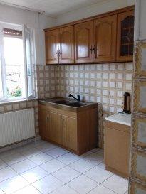 Maison comprenant: cuisine, séjour, 2 chambres, salle de bains/WC, grenier, cave, garage et jardin.