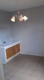 Appartement avec garage comprenant cuisine avec évier et meuble, séjour, chambre et salle d'eau avec WC.