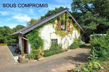 *** SOUS COMPROMIS ***  Charmante maison, isolée, avec annexes, située en zone verte, en lisière de forêt, proche de la rivière sur une parcelle d\'une superficie de 40,60 ares + 58,80 ares de forêt (chênes). Celle-ci a été construite en 1975 et rénovée en 2012. La propriété convient idéalement aux amoureux de la nature. L\'étage 1 représente également un logement intégré complètement équipé (cuisine à installer).  La propriété se compose comme suit:  1) MAISON D\'HABITATION: surface 180 m2  REZ DE CHAUSSEE: - Hall d\'entrée (6,80 m2) - cuisine équipée (10 m2) ouverte sur salon (25 m2) et salle à manger (15 m2) avec accès terrasse - chambre à coucher (18,50 m2) - salle de douche équipée d\'un lavabo (3 m2) - WC séparé (1 m2) - couloir (5 m2) avec accès garage - garage pour 1 voiture (40 m2) (porte: 2,65 x 3,00) avec espace buanderie et chaudière   ETAGE 1: - hall de nuit (8,5 m2) - atelier (41 m2) équipé de 2 Velux + 1 fenêtre - salle de douche (7,31 m2) équipée d\'une douche, WC et lavabo - grenier (8,35 m2) - chambre à coucher I (15 m2) - chambre à coucher II (16,80 m2)  ASPECTS TECHNIQUES: - charpente isolée par l\'extérieur suite à la rénovation de la toiture en 2012 - toiture recouverte d\'ardoises naturelles - chaudière à mazout (VIESMAN) (1990) radiateurs, cuve de 5000 litres  - fosse sceptique (vidage pris périodiquement en charge par la commune) - châssis bois, triple vitrage au rdch et double vitrage au +1 - sols recouvert partiellement de marbre provenant du Sud de l\'Italie - internet - télévision (abonnement Post) - volets battants - 1 cheminée + 1 poêle à bois (séjour)  EXTERIEURS ET ANNEXES:  2) ABRIS DE JARDIN aménagé partiellement en espace rangement p.ex. outillage de jardinage et partiellement équipé d\'un sauna. Equipement: électricité + eau  3) ETABLE en bois à 2 box (5x3 m) pour poneys, ânes ou cheval (1)  Equipement: électricité + dalle en béton  4) JARDIN aménagé d\'un poulailler, d\'une serre pour potager, d\'un abris pour stockage de bûches