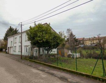 Nous vendons à BERVILLER (57550), à proximité immédiate de la frontière allemande  Une maison de village établie sans mitoyenneté sur un terrain de 6a33 dont une partie peut encore être réservée pour une construction séparée sur une largeur de façade de plus de 10 m .  Elle offre une surface habitable de 137 m2 comprenant notamment :  En plain-pied : Une entrée de 13,46 m2 réalisée dans une extension latérale au bâti d\'origine, Un couloir et dégagements de 11,35 m2 Une pièce à vivre de 12,95 m2 partiellement ouverte sur une kitchenette de 7,71 m2 Un séjour de 11,95 m2 ouvert sur un petit salon de 6,96 m2 Un WC séparé  A l\'étage : Un palier de 10,79 m2 Un dressing de 8,94 m2 donnant accès à une première chambre de 13,07 m2 Trois autres chambres de 15,73 – 12,02 et 10,21 m2 Une salle d\'eau de 4,10 m2.  Avec aussi un espace buanderie et chaufferie à l\'arrière de la maison, des combles non aménagés, une cave.  Ainsi qu\'un garage d\'une longueur de 10,50 m pour le stationnement de deux voitures en alignement. Sa porte est motorisée.  *** Fenêtres en double vitrage sur châssis PVC OB *** Porte d\'entrée récente en PVC avec trois points d\'ancrage *** Chauffage central au fuel *** Raccordé à l\'assainissement collectif  LE BIEN EST IMMEDIATEMENT DISPONIBLE  CONTACT : Gérard STOULIG – Agent commercial au : 06 03 40 33 55  Les frais d\'agence sont à la charge du vendeur.