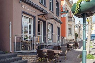 Situé en plein centre de Grevenmacher, ville en plein essor à 20 minutes de Luxembourg-ville, cet immeuble datant de 1930 et entièrement restauré en 2010 accueille actuellement un restaurant offrant de la place pour 50 convives/service sur une surface de ± 120 m².  Rez-de-chaussée: la salle-restaurant avec espace comptoir-bar (caisse et machine à café professionnelle), une véranda avec toit ouvrant, un wc pour personnes à mobilité réduite, un vestiaire avec douche pour le personnel, une buanderie et deux débarras (boissons et réserves).  1er étage: une mezzanine pouvant accueillir quelques tables supplémentaires et la cuisine ± 30 m² professionelle entièrement équipée avec, entre autres, un four au feu de bois (pizzas).  Sous-sol: wc séparés hommes-femmes et local électrique.  La bâtisse inclut également, au 2ème étage, une partie privative comprenant une grande chambre +/- 32 m² avec salle de douche séparée et grande terrasse privative +/- 18 m².  A l'arrière du restaurant (annexe), au 1er étage, un petit studio avec entrée privative incluant un palier d'entrée, une chambre/pièce à vivre et une salle de douche pour le personnel dormant sur place.   Généralités :  - Restaurant à céder en l'état ; - Travaux récents: façade et système de pompe à chaleur pour le chauffage ; - Bombones de gaz pour la cuisine du restaurant ; - Audit énergétique en cours de réalisation ; - Charges: +/- 700-750 € (électricité, chauffage) ; - Parking aisé le long du restaurant + parking communal sur la place.