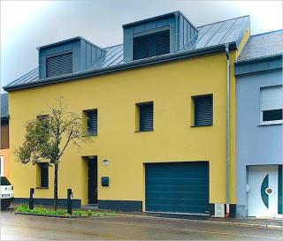 Située à Niederanven, commune recherchée à l'est de Luxembourg-ville, cette maison construite en 2017 dispose d'une surface habitable de ± 273 m² pour une surface totale de ± 341 m² dont un appartement indépendant ±62 m² au rez-de-chaussée avec deux chambres. Elle se compose de la façon suivante :  Le rez-de-chaussée un hall d'entrée ± 12 m² qui donne sur un appartement avec entrée séparée qui se compose comme suit: un séjour de ± 28 m² avec cuisine américaine aménagée et accès à la terrasse de ± 18 m² qui donne sur le jardin, deux chambre ± 12 et 13 m² et une salle de douche de ± 5 m² avec douche italienne, lavabo et wc.Location de l'appartement indépendant entre 1600€ et 1800€.  Le 1er étage se compose d'un séjour de ± 32 m² avec feu ouvert et accès à la véranda ± 18 m², une cuisine aménagée Nolte ± 23 m² avec îlot central et espace salle à manger. Au même étage, la partie nuit comprend la chambre parentale ± 18 m² avec accès à la terrasse, un dressing de ± 6 m² et salle de douche de ± 4 m² avec douche italienne, lavabo et wc, un bureau de ± 10 m² et une autre salle de douche de ± 4 m² avec douche italienne, lavabo et wc.  Le 2è étagecomprend un palier de nuit de ±10 m² qui donne sur 4 chambres ± 9, 10, 23 et 27 m² et entre deux chambres un dressing ± 9 m² avec Velux.  Le sous-sol comprend deux caves de ± 7 et 18 m², une avec le système de la pompe à chaleur et le système de récupération d'eau de pluie (7.500 litres), une buanderie de ± 10 m², un débarras de ± 4 m² et un garage pour deux voitures de ± 29 m².  Généralités:  Maison spacieuse Appartement indépendant Chauffage pompe à chaleur Passeport énergique et isolation: AA Charges mensuelles: électricité 80€/mois, chauffage 20€/mois, eau 10€/mois Commune résidentielle proche du Kirchberg et de l'aéroport Proximité autoroutes